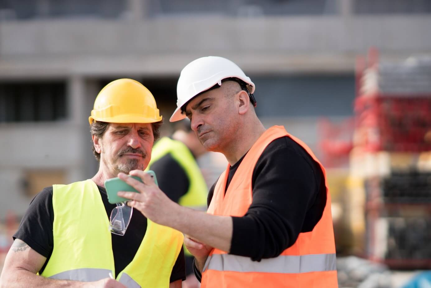Two construction workers with one smartphone