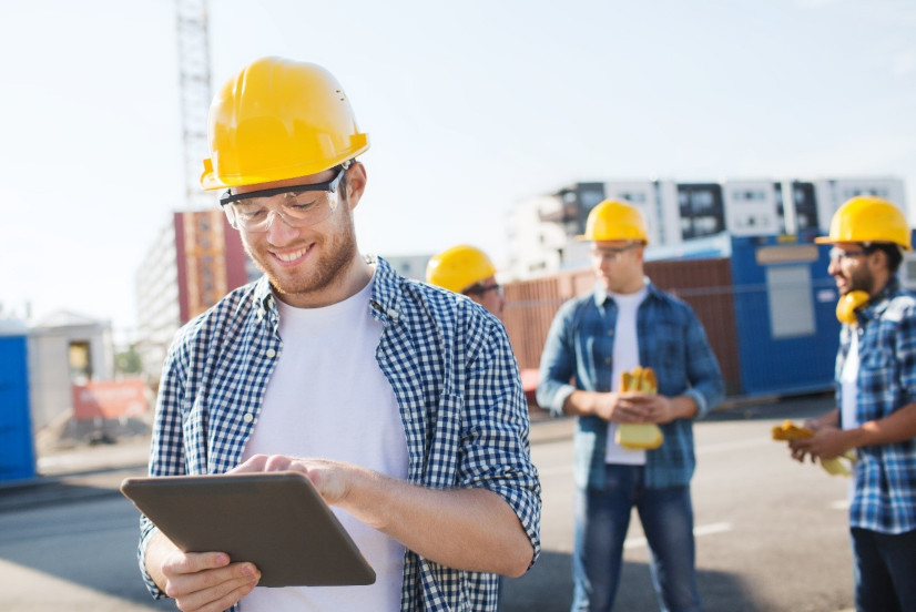 smiling site manager using tablet on construction site