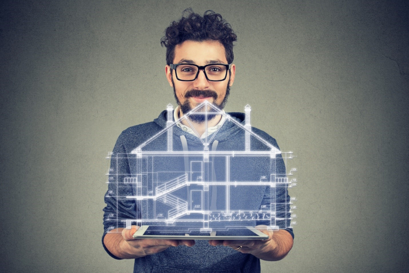 man holding tablet with both hands presenting hologram of a building